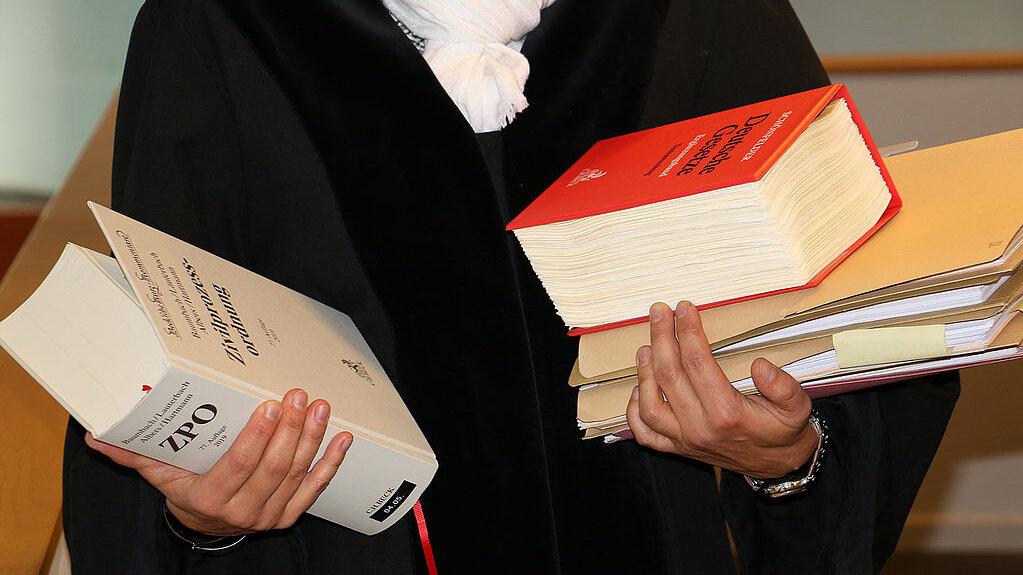 Ausschnitt von einer Richterin mit Robe und Gesetzesbüchern und Akten auf dem Arm